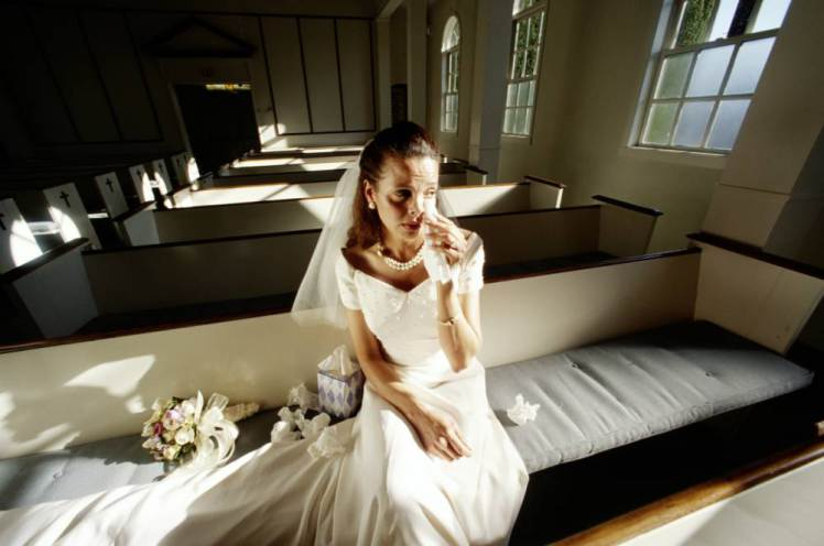Bride crying, sitting on pew in empty church